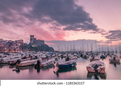 Lerici (La Spezia, Liguria, Italy) at sunset with castle and boats. Pink sky with clouds.