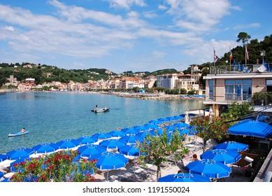 Lerici, La Spezia, Liguria / Italy - June 15 2018: Blue beach umbrellas at San Terenzo.