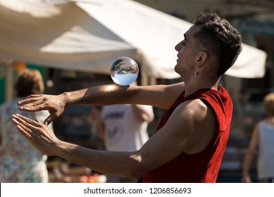 LERICI, LIGURIA, ITALY, JULY 19, 2014: Unidentified young juggler with a crystal ball, shows his art to the public in the Lerici Village, Liguria, italy