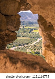 Les Baux, Provence / France - May 14 2014: View of the fields of Provence through a hole in the battlements of Les Baux fortress