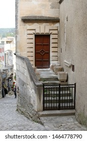 Les Baux-de-Provence, France - OCTOBER 21, 2017: The corner entrance to the old house with a beautiful wooden door and old stone ladder with a metal fence