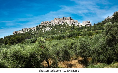 Les Baux-de-Provence historic castle with olive trees in the foreground. Bouches du Rhone, Provence, France, Europe.