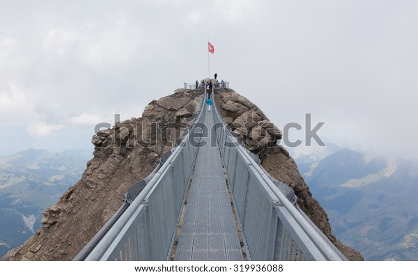 LES DIABLERETS, SWIZTERLAND - JULY 22: People walk at the Glacier 3000 on July 22, 2015. The area houses the world only suspension bridge between 2 mountain peaks.