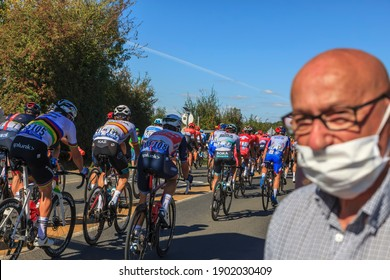 Les Grands Ajoncs, France -September 09, 2020: Unidentified spectator with a face mask in front of the peloton riding during the stage 11 of Le Tour de France 2020.