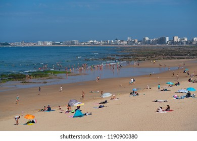 Les Sables d Olonne, 25 July 2018: Chateau d Olonne beach with people and seashore view with Les Sables d Olonne cityscape in background