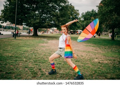 Lesbian bisexual girl with red hair and lgbt flag on her face, colorful mismatched socks, bag and umbrella having fun ooutdoor.