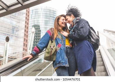 Lesbian couple in Berlin laughing and having fun together. Two beautiful women on the escalator bonding and looking each other. Candid situation with real people. Homosexuality and lifestyle concepts
