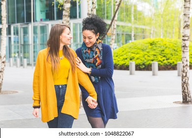 Lesbian couple in Berlin walking and holding hands. Two beautiful women in the city bonding and looking each other. Candid situation with real people.