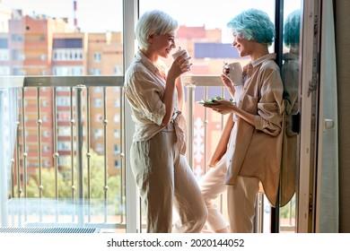 lesbian, couple, breakfast, romance concept. beautiful caucasian lesbian women have breakfast on balcony having talk, enjoying morning together. side view portrait, copy space. people lifestyle - Shutterstock ID 2020144052