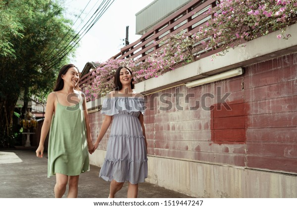 Lesbian couple holding each other hand and walking along the wall.