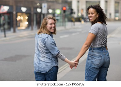 A lesbian couple holding hands looking back