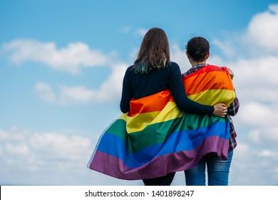 Lesbian couple hugging outdoors. LGBT rainbow flag.