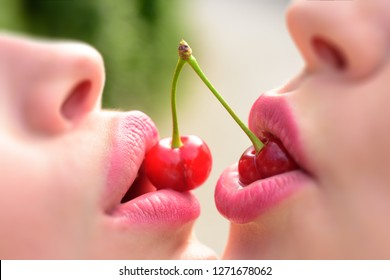 Lesbian couple kiss lips. Sexy lesbian lovers foreplay. Cherry and temptation. Two fruits for two women. Female mouths together close-up
