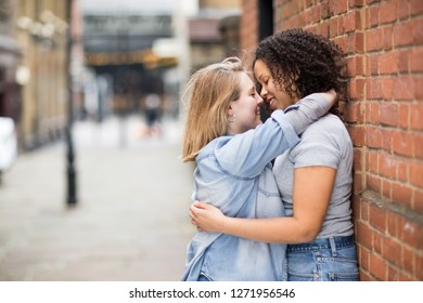 Lesbian couple kissing in the street