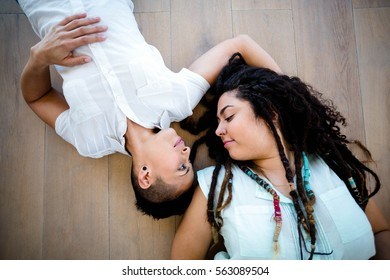 Lesbian couple lying on wooden floor and smiling