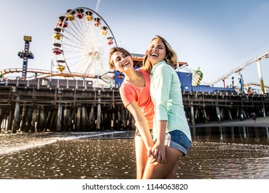 Lesbian couple playing and dating on the beach