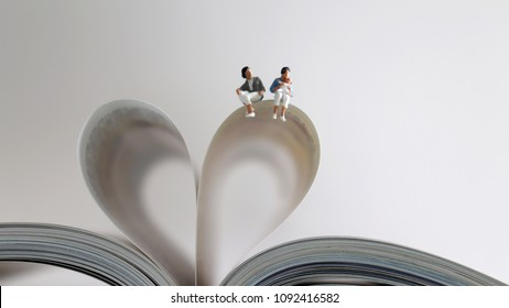 Same-sexcoupleandfamilyloveconcept. Lesbian couple sitting with baby on the book with opened pages and shape of heart.