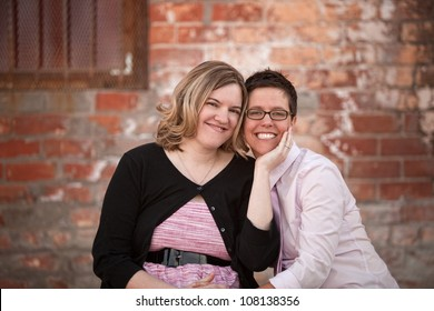 Lesbian couple sitting next to each other outdoors