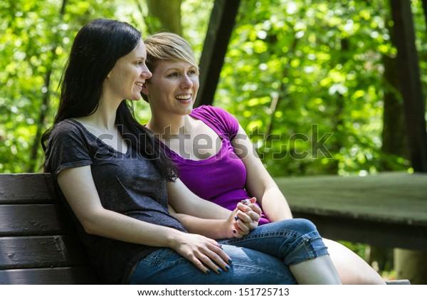 Lesbian couple sitting on park bench, horizontal