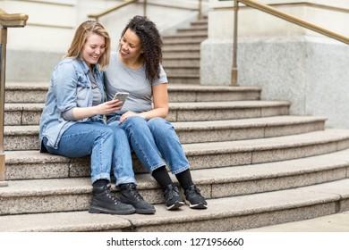 Lesbian couple sitting on steps together