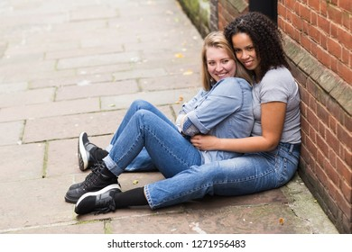 lesbian couple sitting together in the street