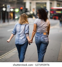 Lesbian couple walking together holding hands in the street
