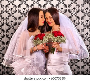 Lesbian couples in wedding bridal dress kissing . same-sex marriage and love couple with flower bunch. Home wallpaper background.