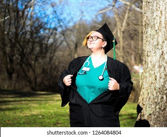 Lesbian Nursing graduate in cap and gown with scrubs and stethoscope underneath