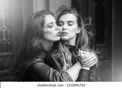 lesbian. Two pretty women or cute girls with closed eyes, stylish makeup and beautiful, long hair hugging outdoors on wooden, front door, vintage color. Lesbian couple. Homosexual love and LGBT