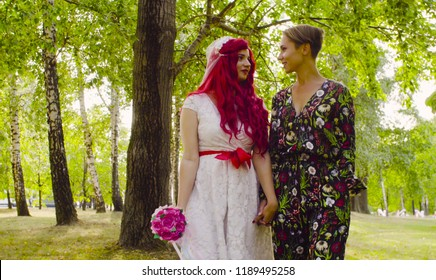 Lesbian wedding. The bride with red hair in a wedding dress and groom are walking in the park hand by hand and talking
