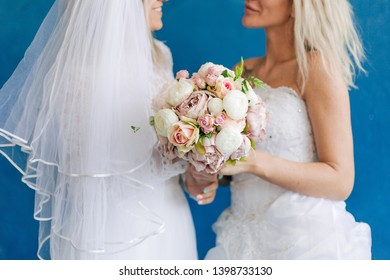 Lesbian in wedding dresses holding bouquet of flowers on blue background close up