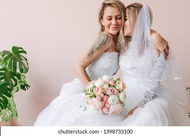 Lesbian wedding hugging in wedding dresses. Love two girls