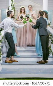 Lesbian wedding. Newlyweds in light pink dresses laughing happily while accepting congrats from friends, bouquets in their hands.  The brides and wedding guests standing on the front porch steps.