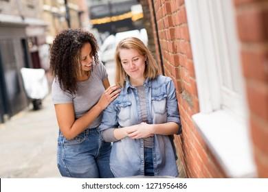 Lesbian woman cheering up her upset girlfriend