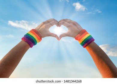 lesbian woman with her hands drawing a heart, in the sky full of clouds and sun rays enter through her hands where she wears gay wristbands with the rainbow flag of lgbt pride