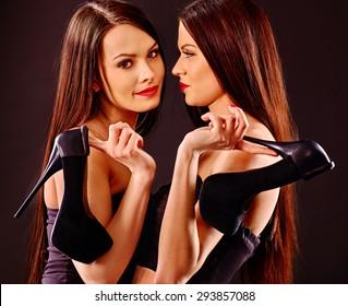 Lesbian women holding louboutin heels shoes as symbol. Black background.