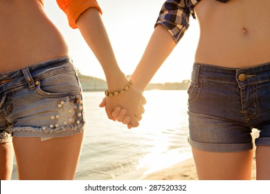 lesbians holding hands at sunset on the beach