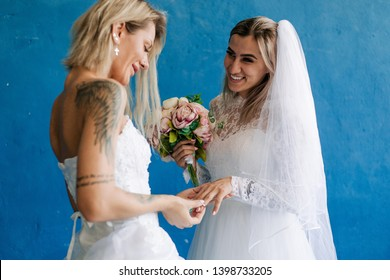 Lesbians in wedding dresses holding a bouquet of flowers put on each other wedding rings. Same-sex wedding of two girls