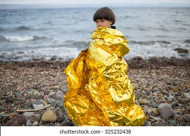 Lesbos, Greece - September 29, 2015: A refugee child uses a thermal blanket to keep warm