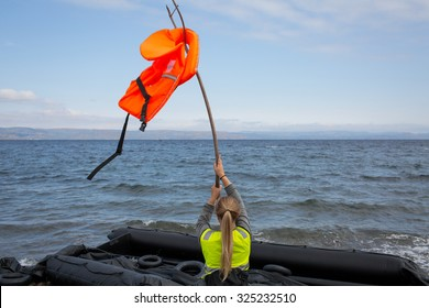 Lesbos, Greece - September 29, 2015: A volunteer uses a life jacket to signal incoming refugee boats