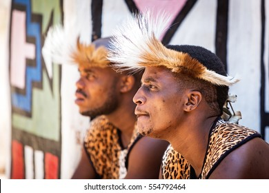 LESEDI CULTURAL VILLAGE, SOUTH AFRICA - NOVEMBER 4, 2016. Two young male Zulu tribe members wearing traditional warrior leopard skin garments and headdresses