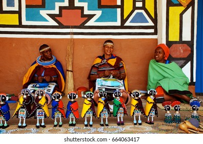 LESEDI VILLAGE, SOUTH AFRICA - JANUARY 1, 2008: African ndebele women wearing traditional handmade accessories sell traditional dolls in Lesedi African Lodge and Cultural village, South Africa
