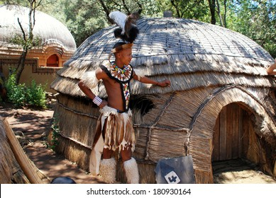 LESEDI VILLAGE, SOUTH AFRICA-JAN 1,2008:Zulu man wearing warrior dress near tribal straw house in Lesedi Cultural village, South Africa. Men in Zulu clan wear animal skin decorated multicolored beads.