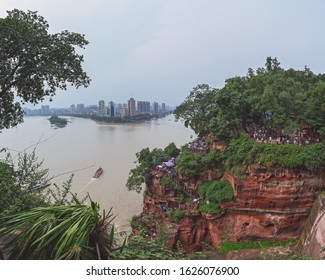 Leshan, China -  July 2019 : Tourists going down stairs to the Leshan Giant Buddha with the view of the Leshan town,  at the confluence of the Min River and Dadu River in the southern part of Sichuan