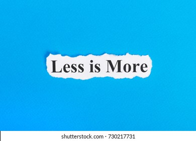 less is more text on paper. Word less is more on torn paper. Concept Image.