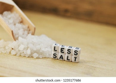Less salt recommendation with wooden spoon and granulated salt on beige background