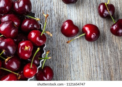 Less than perfect red cherries in a tin dish on a wooden table