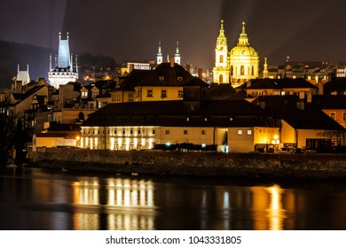 Lesser town bridge tower, Strahov monastery, St. Nicholas Church and Vltava river in Prague, Czech republic. Night scene. Travel destination.