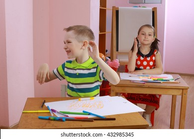 a lesson in class with a hyperactive child. hyperactive boy. the child indulges in the classroom. misbehaves. teacher talking to student. the boy waved his hands and turning his head. hyperactive boy