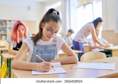 Lesson in class of teenage children, in front girl 13, 14 years old sitting at desk writing in notebook. Education, school, college, schoolchildren concept